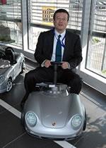 ポルシェ博物館で売っているおもちゃの車に乗る社長