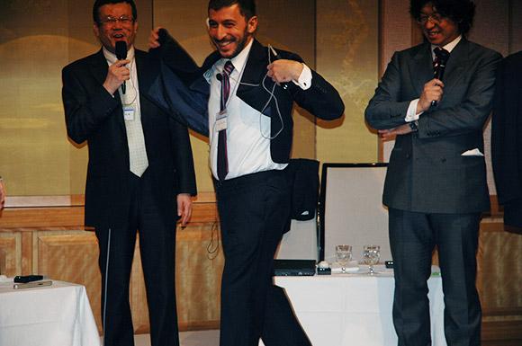 ケアメンテした自分のスーツの軽さに驚くアンジェロ・ペコラ氏(第一回環境と洗浄の世界大会にて)